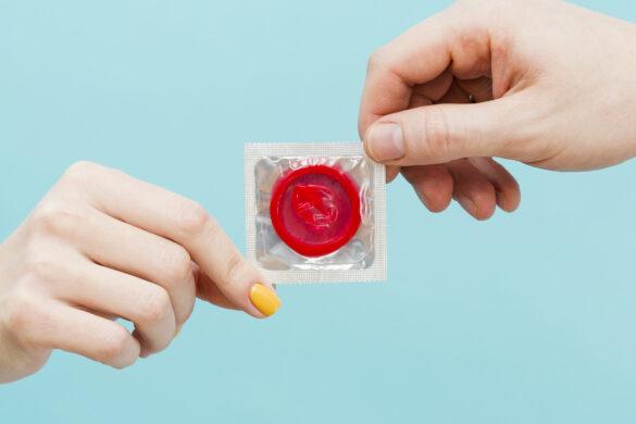 Tipos de DST: foto de duas mãos (uma de um homem e outra de uma mulher) segurando um preservativo vermelho