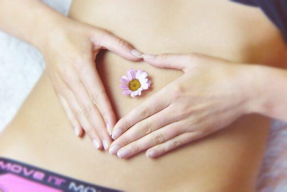 Endometriose: foto de uma mulher com as mãos sob o abdome com uma flor no centro da barriga